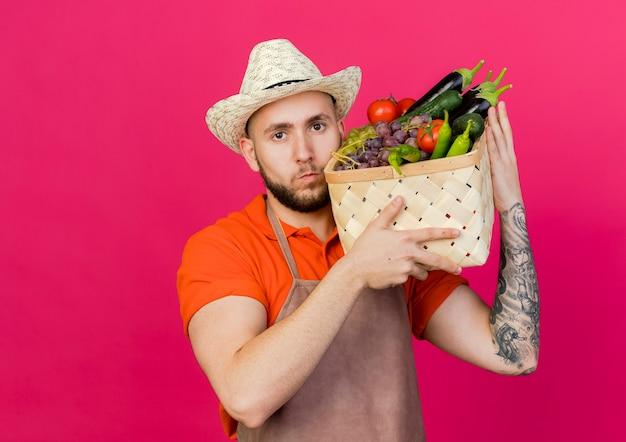 Selbstbewusster männlicher gärtner, der gartenhut trägt, hält gemüsekorb auf schulter