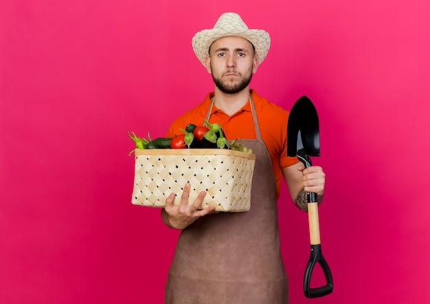 Selbstbewusster männlicher gärtner, der gartenhut trägt, hält gemüsekorb und spaten