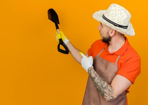 Selbstbewusster männlicher gärtner, der gartenhut trägt, hält spaten, der nach hinten schaut und zeigt
