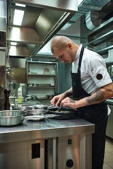 Selbstbewusster männlicher koch in schwarzer schürze, der sein gericht in einer restaurantküche garniert