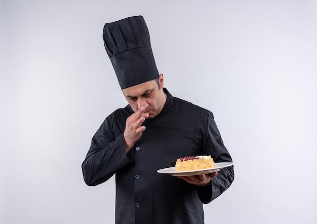 Selbstbewusster männlicher koch mittleren alters in der kochuniform, die kuchen auf teller betrachtet, der köstliche geste auf isolierter weißer wand mit kopienraum zeigt