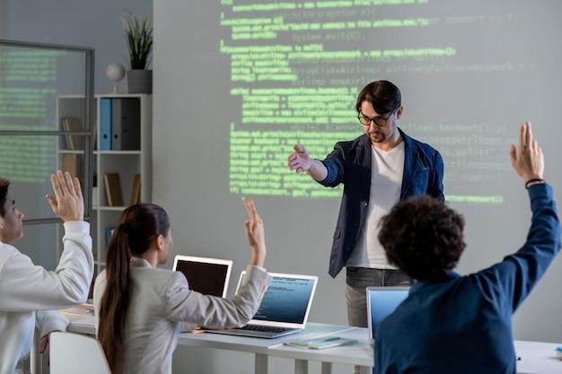 Selbstbewusster männlicher lehrer, der auf einen der schüler in der ersten reihe zeigt, während sie seine frage während der präsentation beantworten lässt