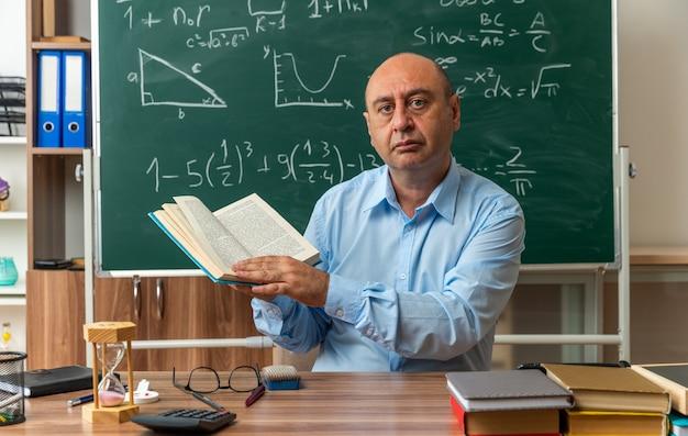 Selbstbewusster männlicher lehrer mittleren alters sitzt am tisch mit schulmaterial, das ein buch im klassenzimmer hält