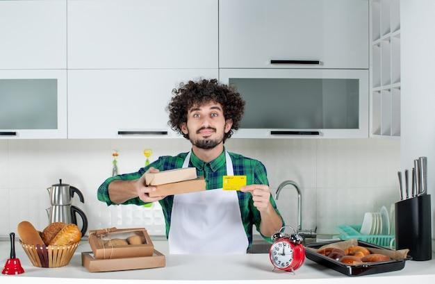 Selbstbewusster mann, der hinter dem tisch verschiedene gebäckstücke darauf steht und braune kisten mit bankkarten in der weißen küche hält