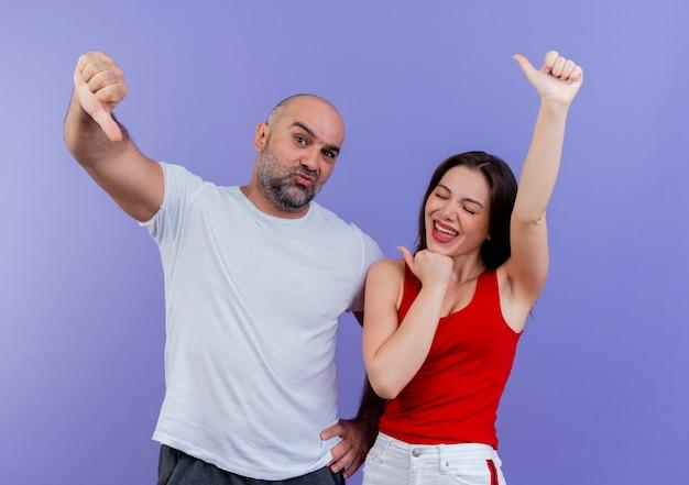 Selbstbewusster mann des erwachsenen paares, der hand auf taille und freudige frau mit geschlossenen augen hält, die beide daumen hoch zeigen