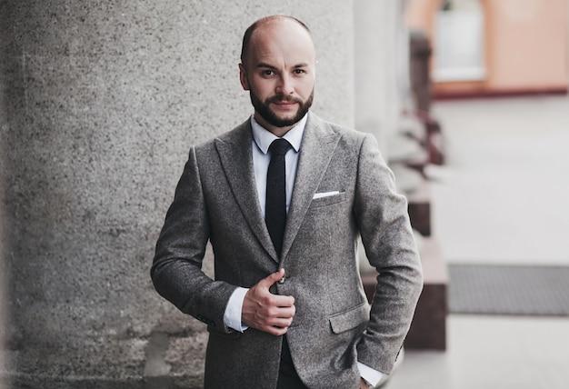 Selbstbewusster mann im anzug posiert vor dem hintergrund der stadt. konzept einer immobilienmanager- oder anwaltskarriere