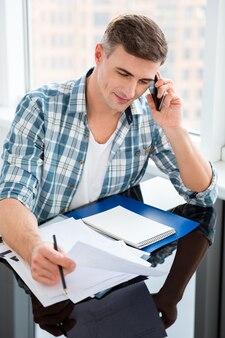 Selbstbewusster mann in kariertem hemd, der mit rechnungen am tisch sitzt und am handy spricht