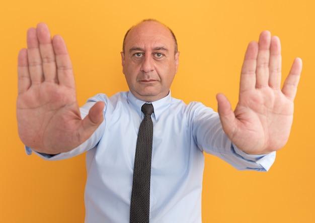 Selbstbewusster mann mittleren alters, der weißes t-shirt mit krawatte trägt, die hände heraus an der front lokalisiert auf orange wand hält