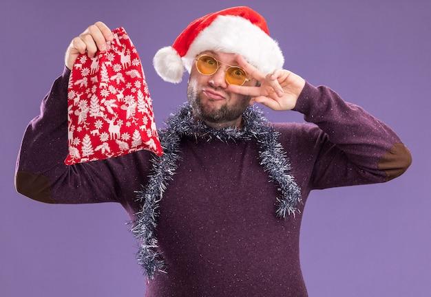 Selbstbewusster mann mittleren alters mit weihnachtsmütze und lametta-girlande um den hals mit brille, die einen weihnachtsgeschenksack hält und in die kamera schaut, die das v-zeichen-symbol in der nähe des auges einzeln auf violettem hintergrund zeigt isolated