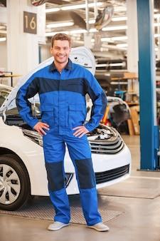 Selbstbewusster mechaniker. voller länge des gutaussehenden jungen mannes, der die hände auf der hüfte hält und lächelt, während er in der werkstatt mit dem auto im hintergrund steht