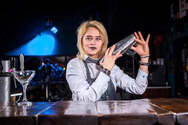 Selbstbewusster mixologe, der frisches alkoholisches getränk in die gläser im nachtclub gießt