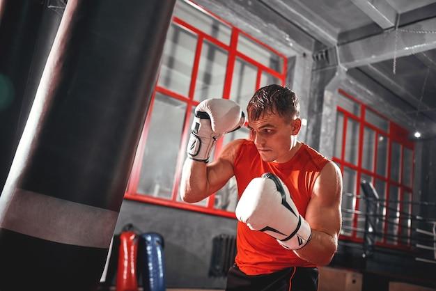 Selbstbewusster muskulöser sportler in sportbekleidung hartes training auf schwerem boxsack. junger boxer mit weißen boxhandschuhen im schutzständer auf rotem fensterhintergrund
