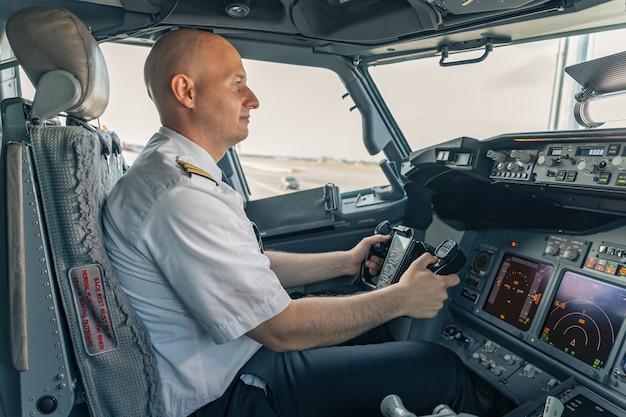 Selbstbewusster pilot, der im cockpit sitzt und das lenkrad hält