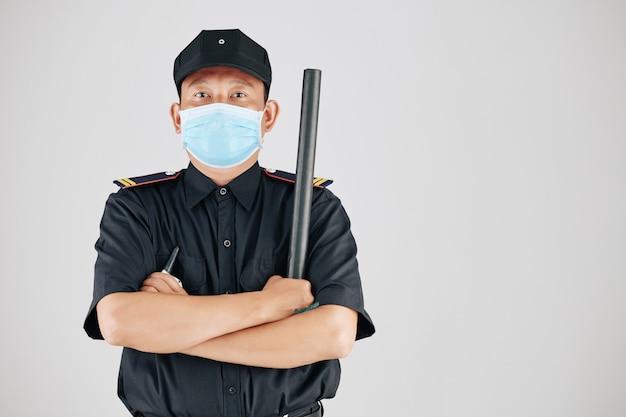 Selbstbewusster polizist in medizinischer maske