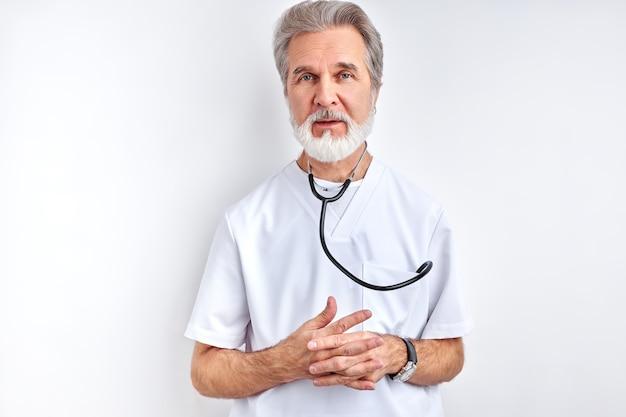 Selbstbewusster professioneller apothekenexperte des bärtigen mannes mit stethoskop, isoliert auf hellweißer farbe