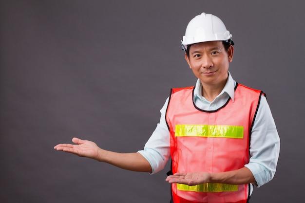 Selbstbewusster, professioneller asiatischer mann, der hand nach oben und weg zeigt, konzept des männlichen ingenieurs, des zivilbaus, des bauherrn, des architekten, des arbeiters, des mechanikers, des elektrikers, der hand auf leerzeichen zeigt oder zeigt