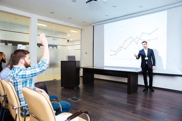 Selbstbewusster redner im gespräch mit dem publikum über business-training im konferenzsaal talking