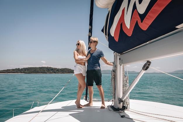 Selbstbewusster reicher und erfolgreicher mann und frau posieren auf ihrer yacht, umarmen sich und betrachten die landschaften