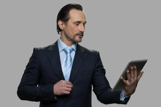 Selbstbewusster reifer geschäftsmann, der digitales tablett verwendet. erfolgreiche kaukasische exekutive, die video-chat gegen grauen hintergrund hat. konzept für menschen, unternehmen und online-kommunikation.