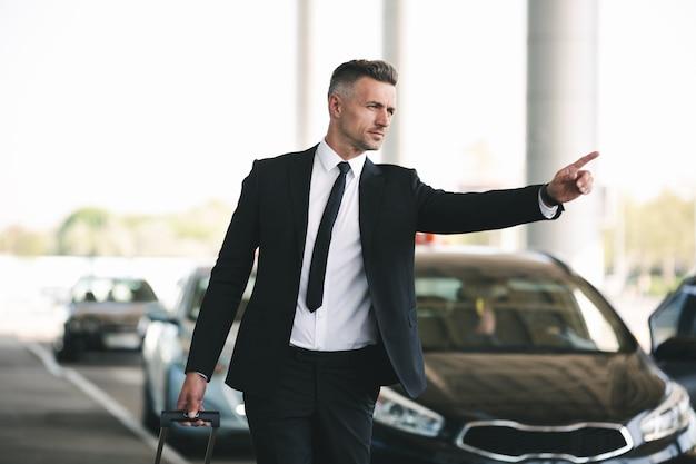 Selbstbewusster reifer geschäftsmann, der ein taxi fängt