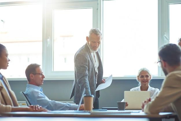 Selbstbewusster reifer geschäftsmann oder chef, der projektergebnisse mit dem team im modernen büro bespricht
