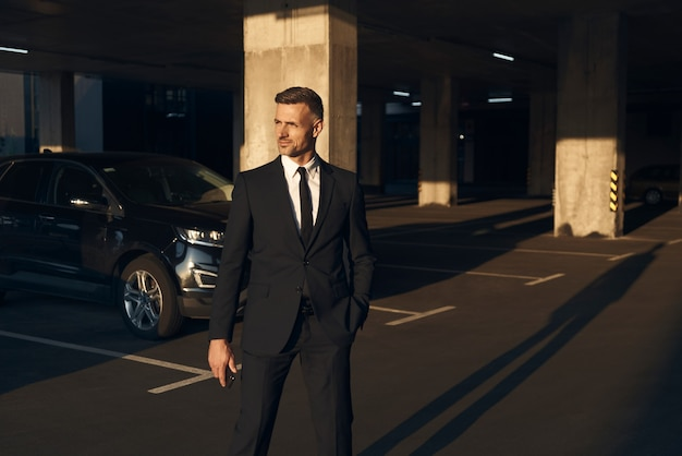 Selbstbewusster reifer mann im vollen anzug, der am parkplatz vorbeigeht