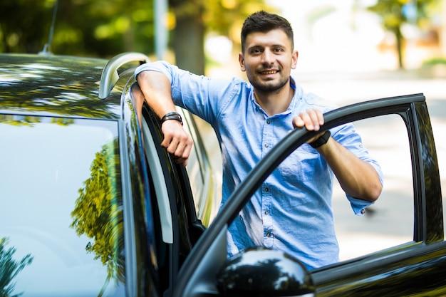 Selbstbewusster reifer mann in abendgarderobe, der die autotür öffnet