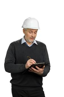 Selbstbewusster reifer supervisor, der in die zwischenablage schreibt. älterer mann im weißen helm, der auf schwarzer zwischenablage schreibt