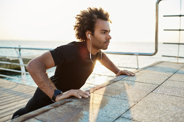 Selbstbewusster sportler mit buschiger frisur, der am frühen morgen übungen am pier macht. er legte seine arme auf die plattform, während er musik hörte.