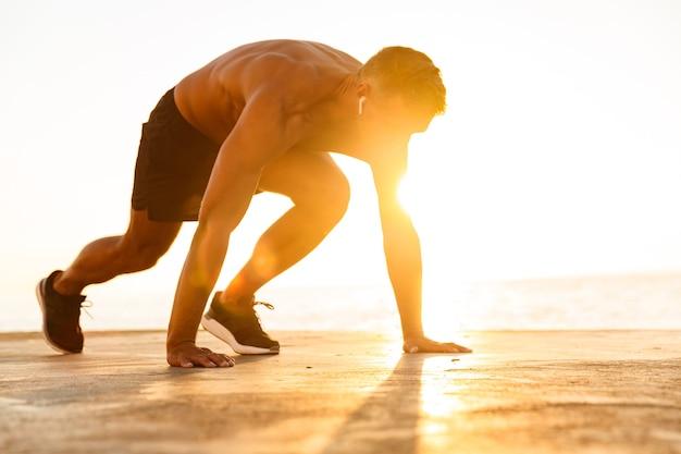 Selbstbewusster sportler mit kopfhörern, die sich zum laufen vorbereiten