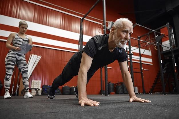 Selbstbewusster sportlicher sechzigjähriger mann mit bart, der liegestütze tut, die stilvolle schwarze sportkleidung tragen, während sein trainer mit klemmbrett seine ergebnisse aufschreibt. alter, ruhestand, gesundheit und vitalität