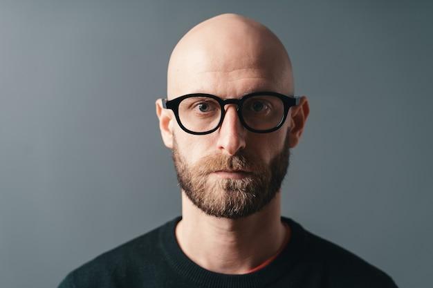 Selbstbewusster stilvoller junger bärtiger mann der nahaufnahmeporträt, der brille mit schwarzem rahmen trägt