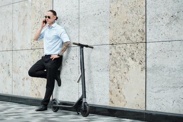 Selbstbewusster stilvoller junger unternehmer, der sich an die wand neben seinem roller lehnt und am telefon anruft