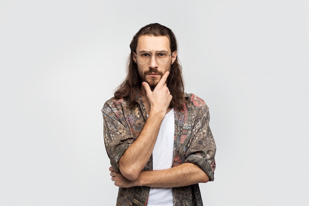 Selbstbewusster typ mit brille und coolem hemd mit langen haaren, hübscher kerl. kreative person. stilvoller sorgloser mann des hipster-reisenden auf einem weißen studiohintergrund, menschenlebensstil