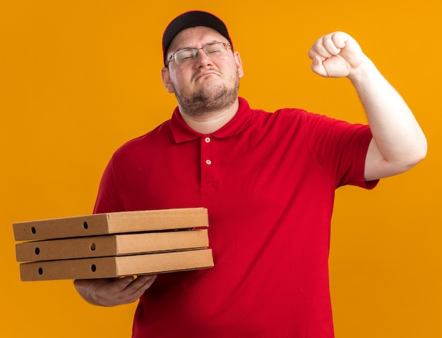 Selbstbewusster übergewichtiger junger lieferbote in optischen gläsern, die pizzaschachteln halten und faust isoliert auf orange wand mit kopienraum halten