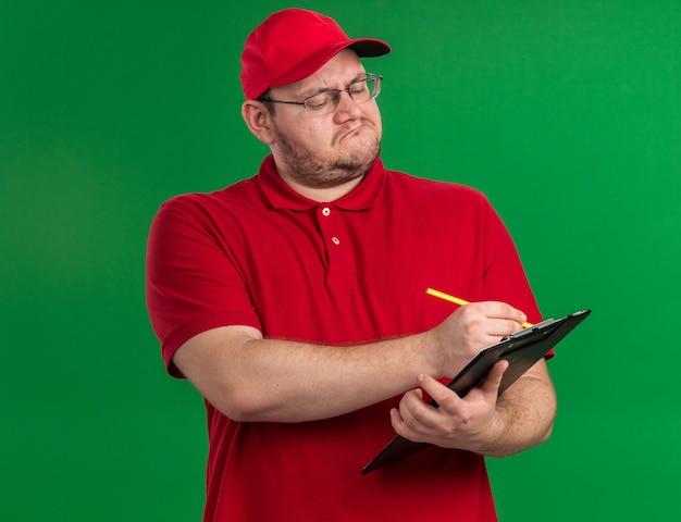 Selbstbewusster übergewichtiger junger lieferbote in optischer brille, der mit bleistift auf zwischenablage schreibt, isoliert auf grüner wand mit kopierraum