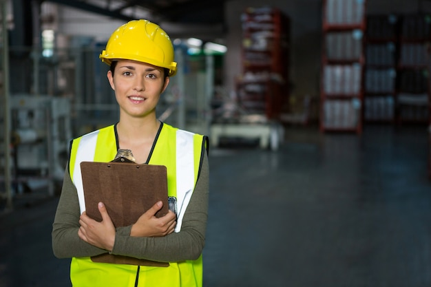 Selbstbewusster weiblicher arbeiter, der zwischenablage im lager hält
