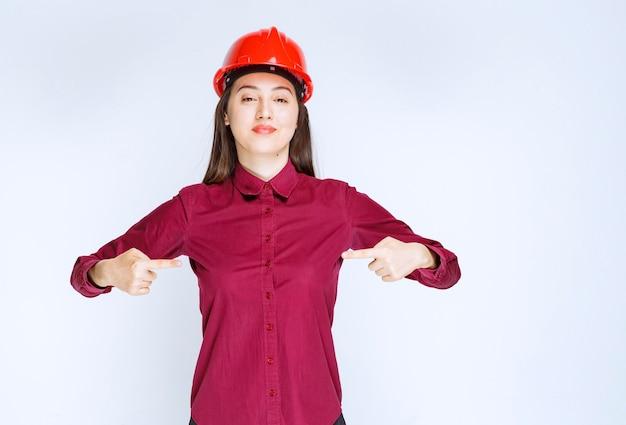 Selbstbewusster weiblicher architekt im roten harten helm, der steht und zeigt.