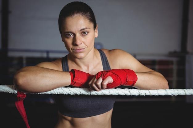 Selbstbewusster weiblicher boxer, der sich auf boxring stützt