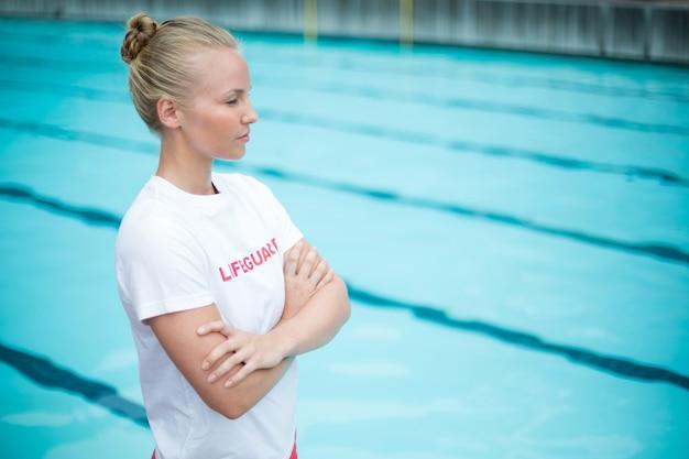 Selbstbewusster weiblicher rettungsschwimmer, der am pool steht