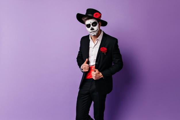 Selbstbewusster zombietyp, der mit rose auf hut aufwirft. innenfoto des interessierten mannes mit schädel-make-up, das für halloween-partei vorbereitet.