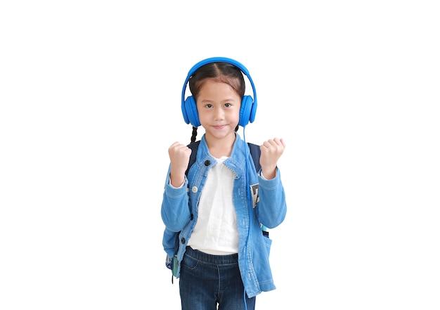 Selbstbewusstes asiatisches kleines mädchen heben hand auf, genießen mit smartphone und kopfhörern lokalisiert auf weiß
