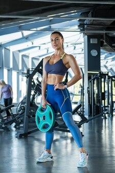 Selbstbewusstes, fittes mädchen, das mit hantelscheibe im fitnessstudio steht