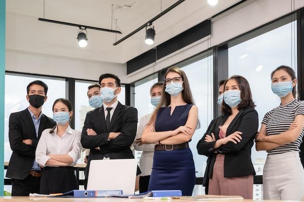 Selbstbewusstes geschäftsteam von multiethnic, das mit verschränktem arm steht und medizinische maske im modernen büro trägt