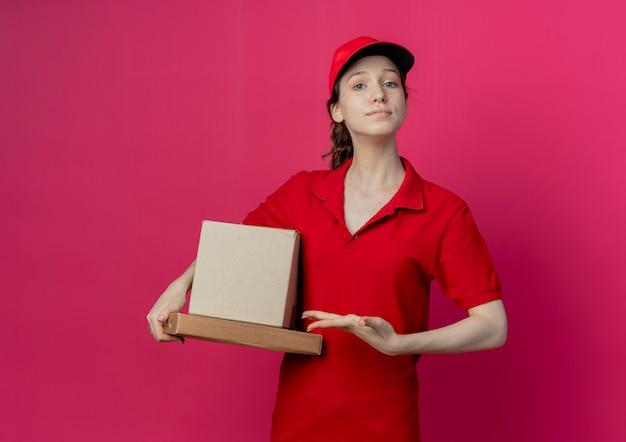 Selbstbewusstes hübsches junges liefermädchen, das rote uniform und kappe hält und mit der hand auf kartonschachtel und pizzapaket zeigt, lokalisiert auf purpurrotem hintergrund mit kopienraum