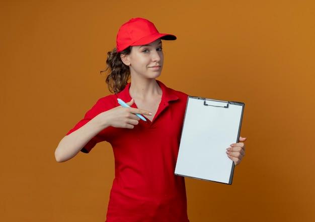 Selbstbewusstes hübsches junges liefermädchen in der roten uniform und in der kappe, die stift und zwischenablage halten und auf zwischenablage zeigen, lokalisiert auf orange hintergrund mit kopienraum