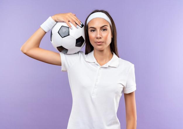 Selbstbewusstes hübsches sportliches mädchen mit stirnband und armband, das fußball auf der schulter hält, isoliert auf lila wand