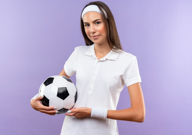 Selbstbewusstes hübsches sportliches mädchen mit stirnband und armband, das fußball isoliert auf lila wand hält