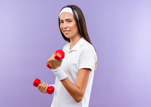 Selbstbewusstes hübsches sportliches mädchen mit stirnband und armband, das hanteln isoliert auf lila wand mit kopienraum hält holding