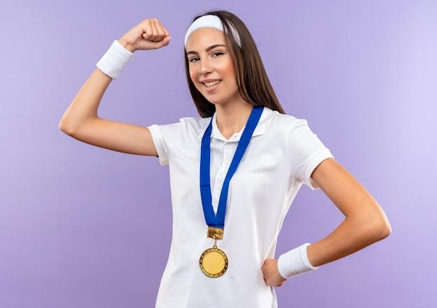 Selbstbewusstes hübsches sportliches mädchen mit stirnband und armband und medaille, die stark mit der hand an der taille gestikuliert, isoliert auf lila wand